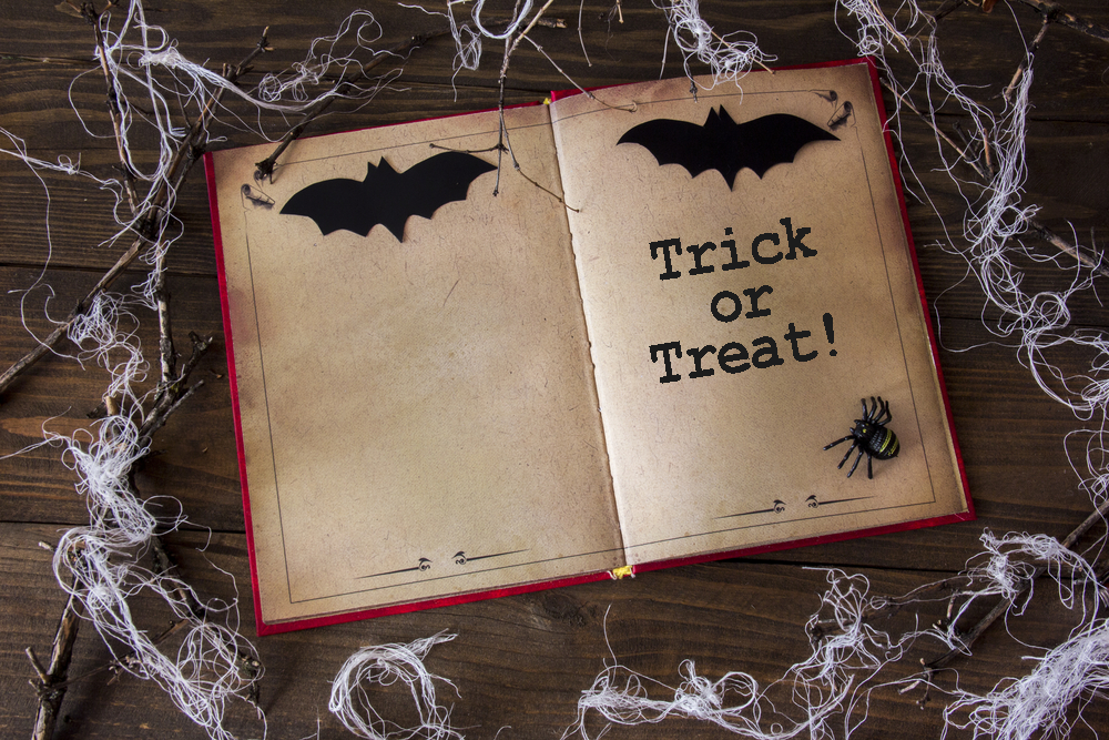 Spooky book with the words trick or treat on a table with bats and spider webs