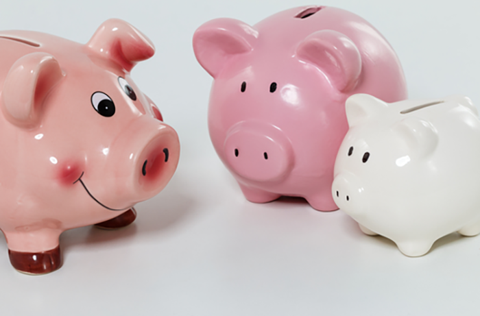 Three pink piggy banks of different sizes